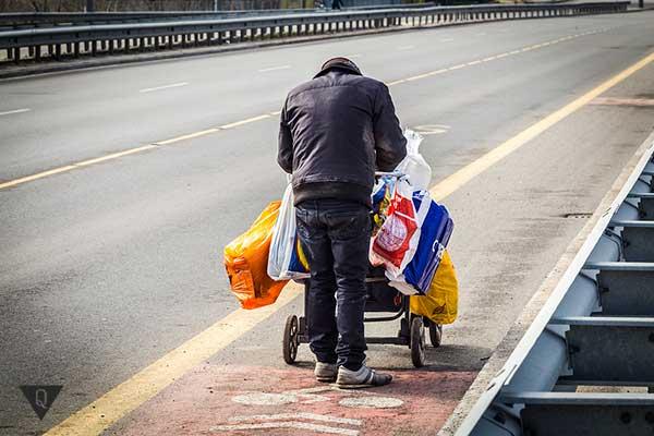 Бездомный везет тележку с хламом