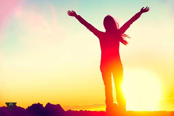 Девушка поднимает руки на закате