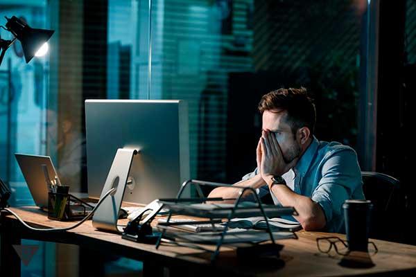 Уставший мужчина работает за компьютером