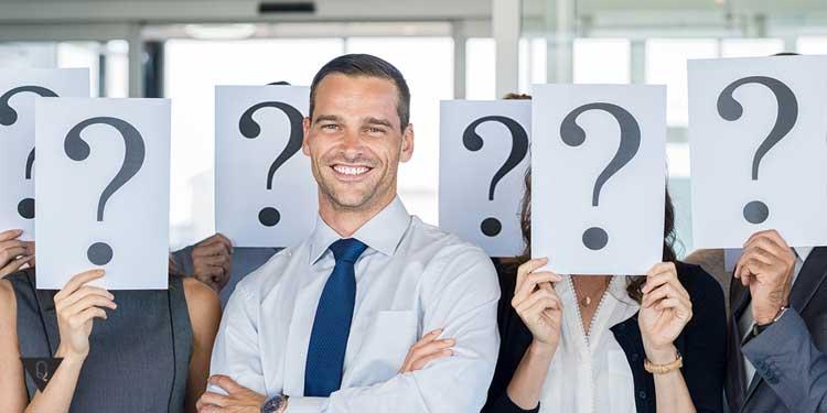 Мужчина в деловом костюме на фоне людей со знаком вопроса