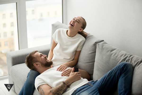 Мужчина лежит у смеющейся женщины на коленях