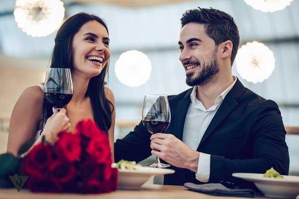 Женщина и мужчина пью вино и смеются