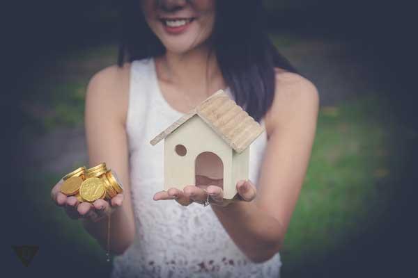 девушка держит в руках деньги и дом, как символ материальных ценностей, и духовных