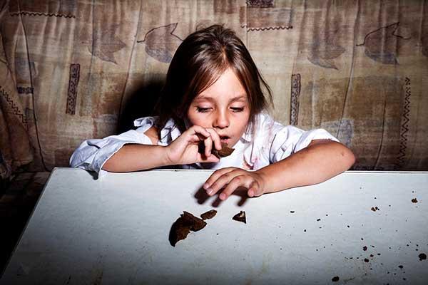 Девочка из бедной семьи ест хлеб