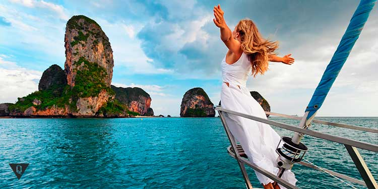 девушка стоит на носу яхты