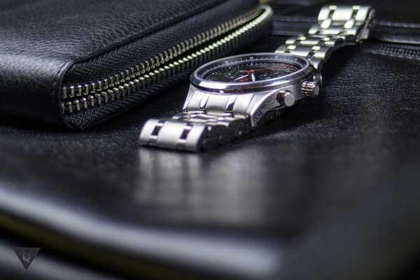 Черный кошелек и часы на столе