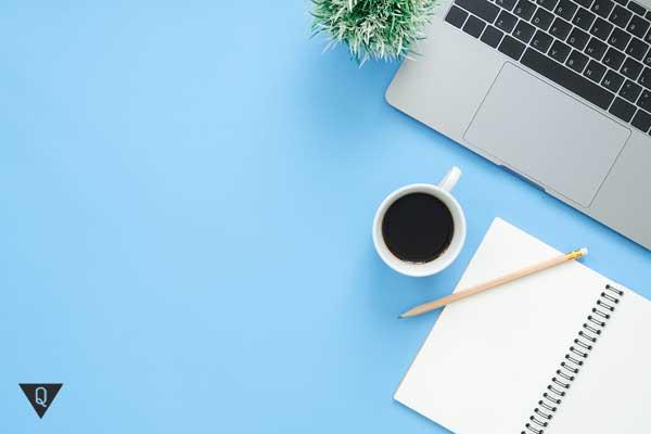 Ноутбук, чашка кофе и блокнот на голубом фоне