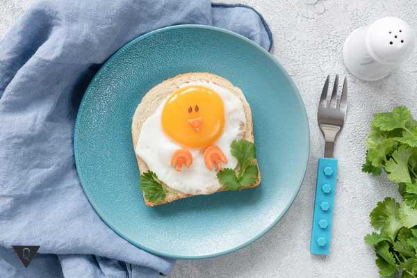 Голубая тарелка с яичницей на голубой скатерти