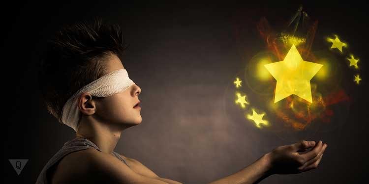 Парень с завязанными глазами протянул руки к шару из звезд в знак того, что обладает интуицией
