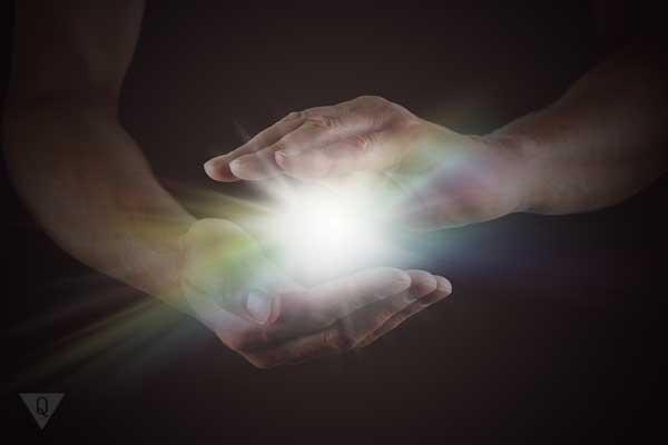 В руках белый шар из света