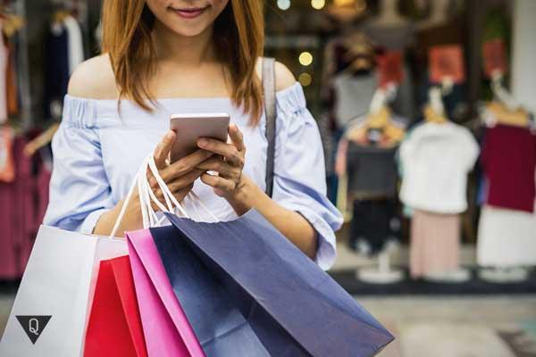 Девушка с покупками и мобильным телефоном