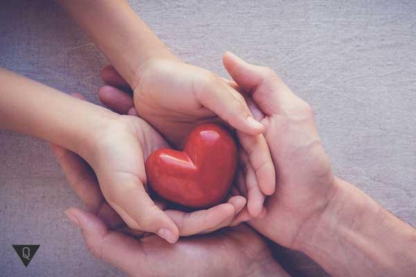 Игрушечное сердце в мужских и женских руках