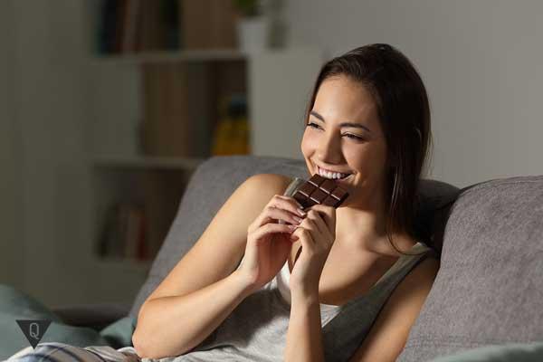 девушка с удовольствием ест шоколад в кровати