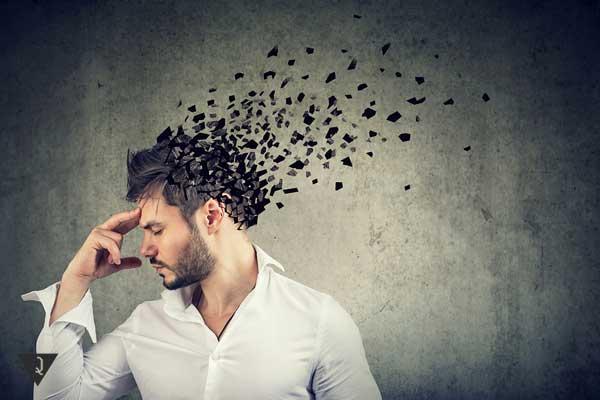 Мужчина, от головы которого отлетают части, как символ потери памяти
