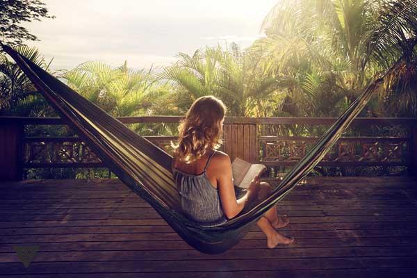 Девушка читает книгу в гамаке