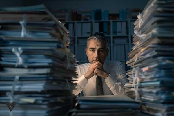 Работник с двумя кучами бумаг на столе
