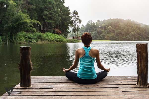 Девушка концентрируется, медитирует на берегу реки
