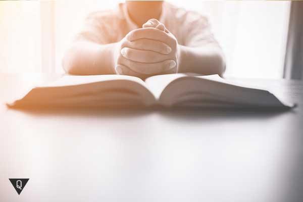 Мужчина за столом читает книгу