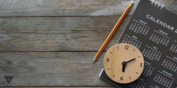 На столе часы и ежедневник с карандашом