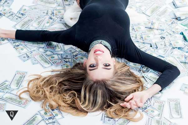 Молодая женщина лежит на долларах