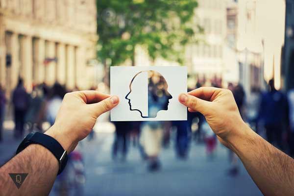 Мужчина держит в руках картинку с двумя лицами