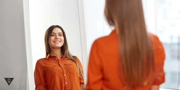 Девушка перед зеркалом улыбается, выполняя артикуляционные упражнения