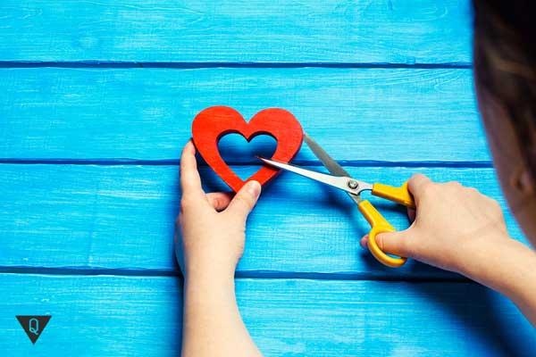 Девушка разрезает ножницами сердце