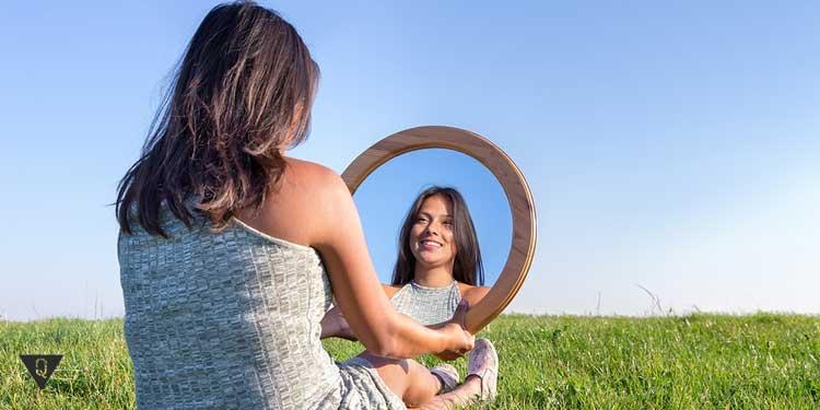Девушка на поляне смотрит на себя в зеркало
