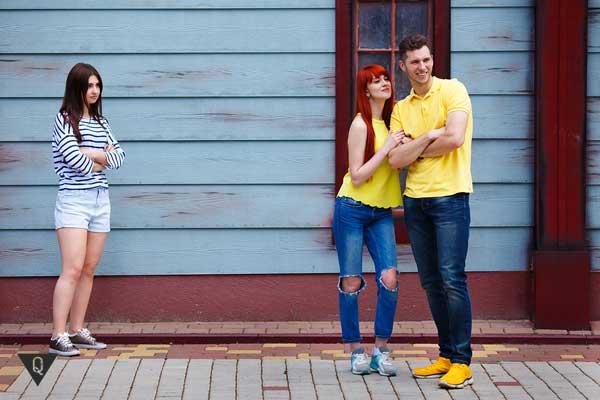 Девушка смотрит как пара позирует фотографу