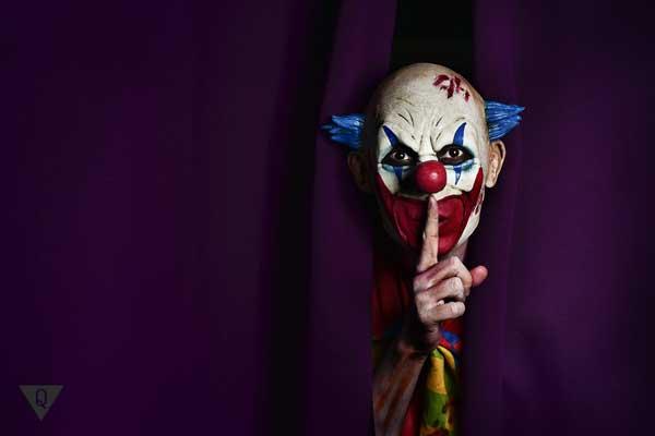 Клоун из-за кулис держит палец у рта