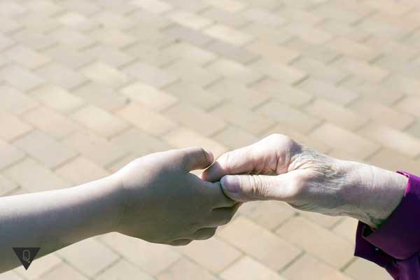 Бабушка и внучка держат друг друга за руку