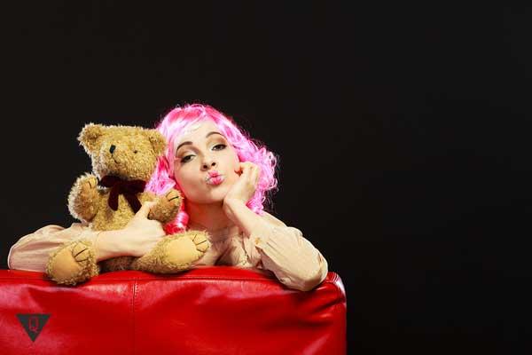 Женщина с розовыми волосами и мягкой игрушкой
