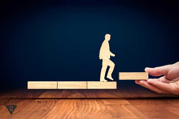 Деревянный человечек продвигается вперед по ступенькам