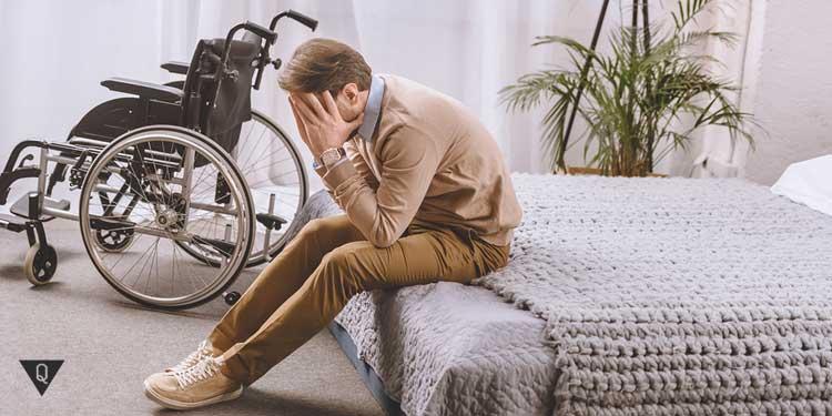 Мужчина с ограниченными возможностями сидит на кровати