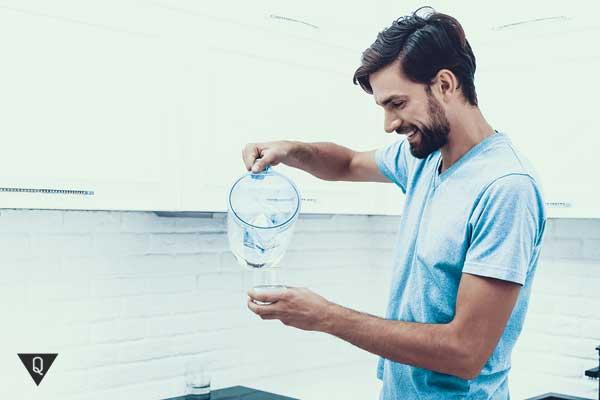 Мужчина наливает воду в стакан