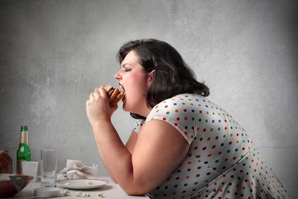 Полная женщина ест гамбургер
