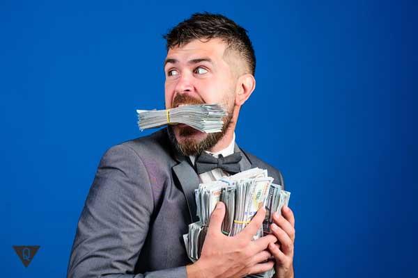 Мужчина держит деньги во рту и руках
