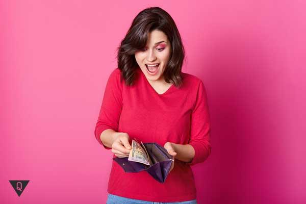 Девушка открыла кошелек и радуется деньгам
