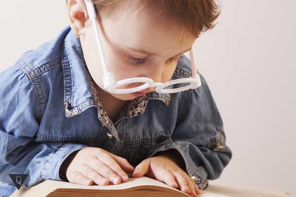 Маленький мальчик в очках читает книгу