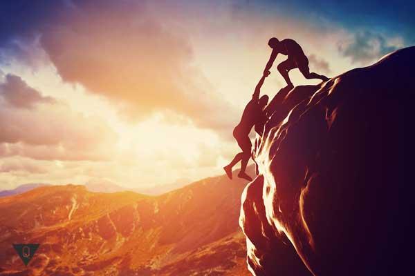 Мужчина поднял другого на вершину горы