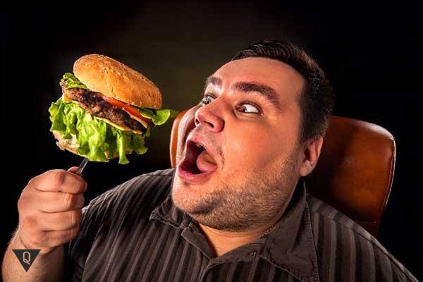 Полный мужчина ест гамбургер