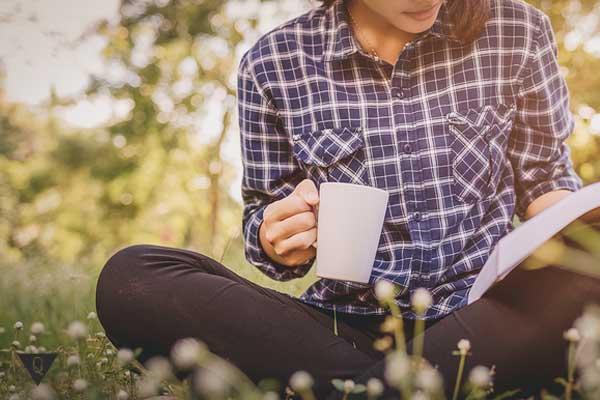 Девушка с чашкой на природе читает книгу
