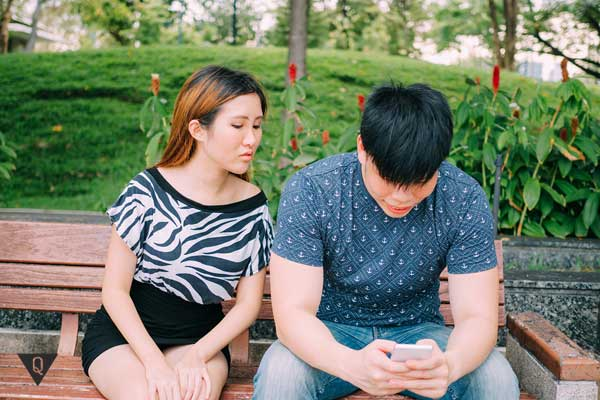 Девушка заглядывает в телефон к парню