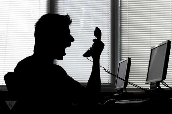 Мужчина кричит в трубку телефона