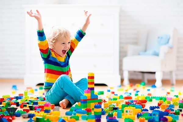 Ребенок радуется играя в конструктор лего