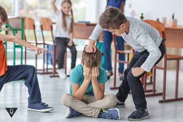 Агрессивный мальчик обижает одноклассника