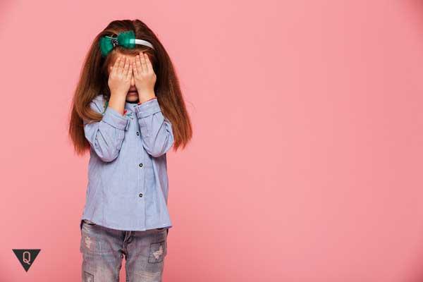 Девочка плачет, закрыв лицо руками