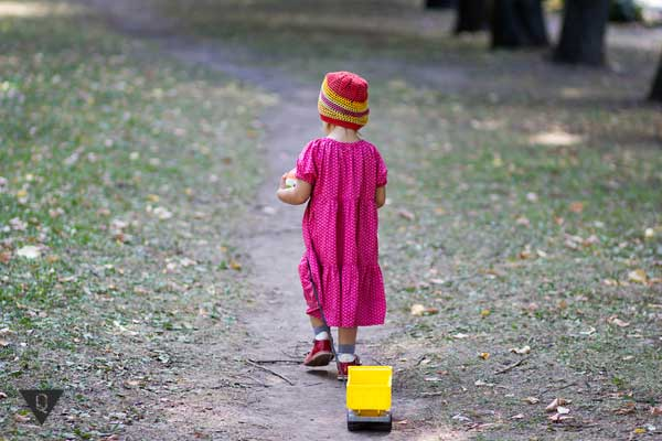 Девочка идёт и тянет за собой машинку