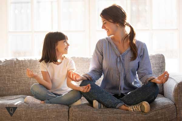 Мама с дочкой медитируют на диване