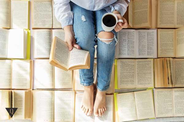 Девушка сидит на разложенных на полу книгах и читает